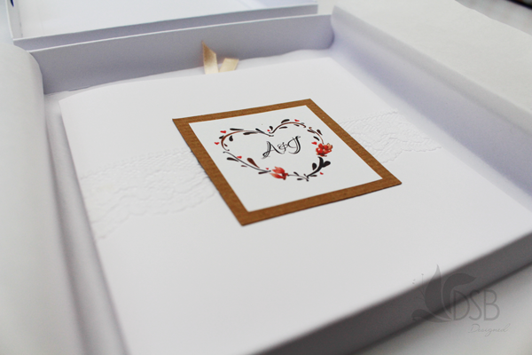 Wedding invitation nestled in its box wrapped in tissue paper.