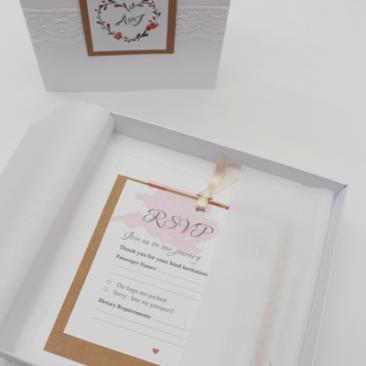 Boxed wedding invitations opened revealing layered inserts.