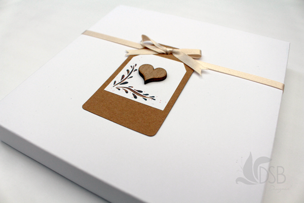 Invitations in boxes and tied with a nude ribbon and tag ready to be addressed.